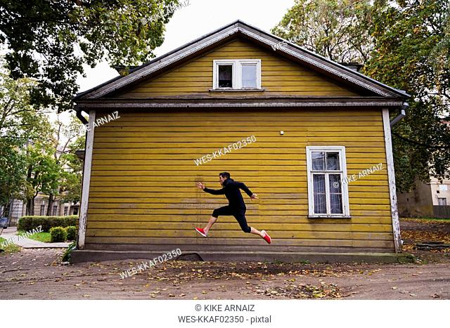 Dynamic athlete jumping in front of a yellow wood house