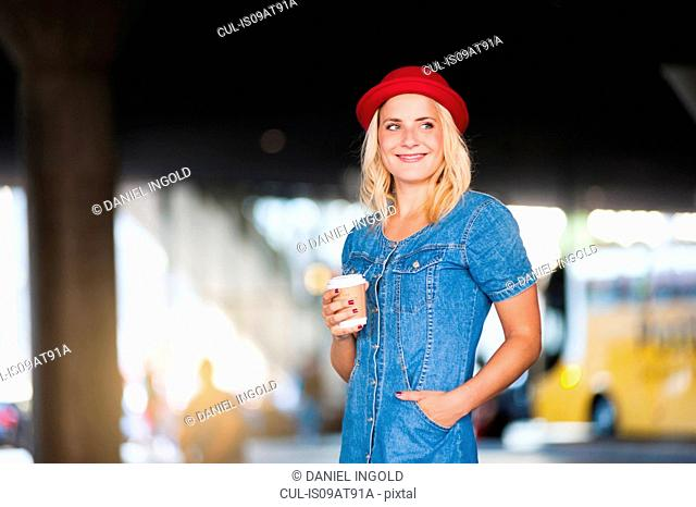 Young woman wearing red hat waiting in bus station