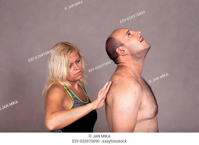 Profile of blonde woman giving a back massage to shirtless man