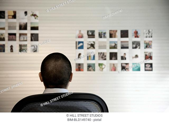 Pacific Islander businessman looking at pictures on wall