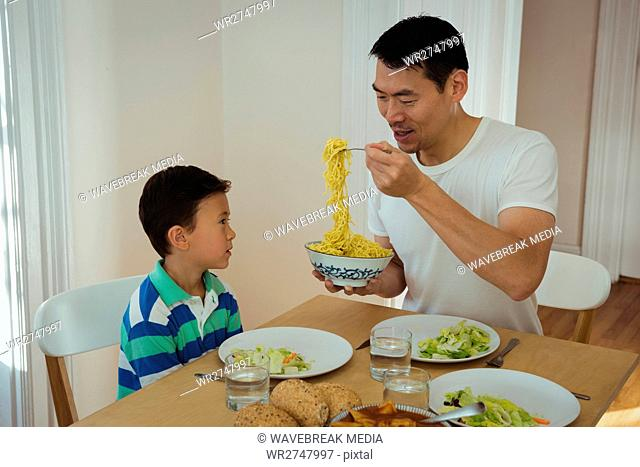 Father serving food to his son on dining table