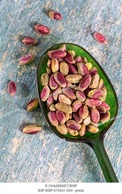 peeled pistachio nuts in a green spoon, isolated, wooden background