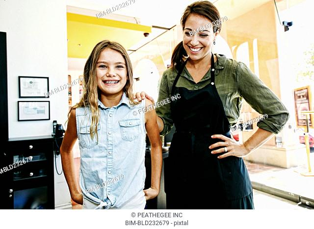 Smiling hairdresser and customer posing in hair salon