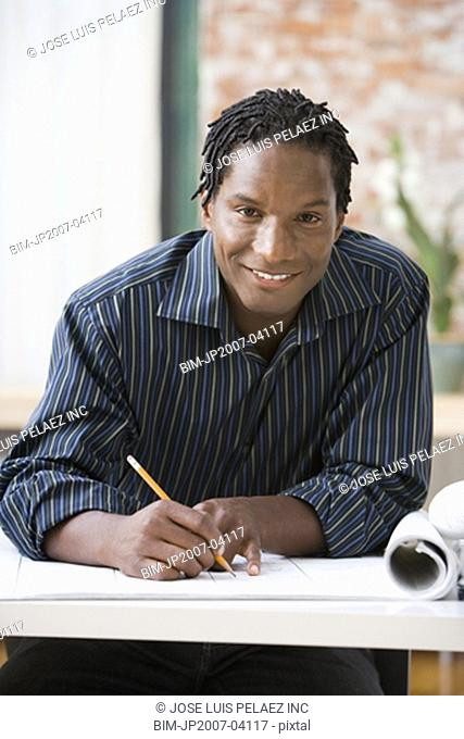 African businessman writing on blueprints