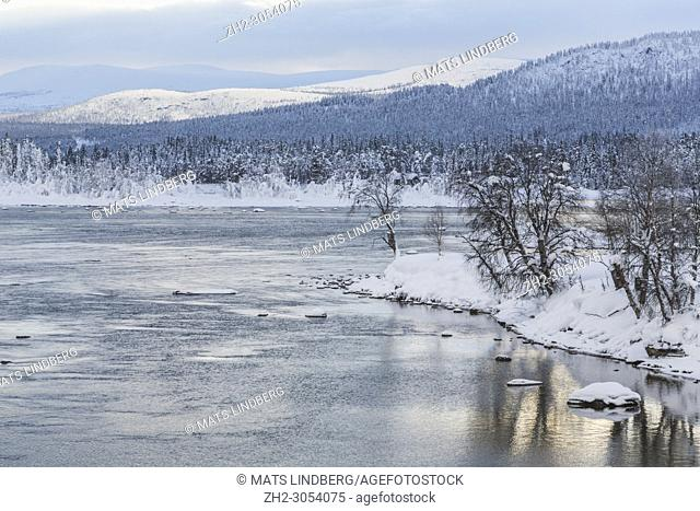 Winter landscape in Tjåmotis with mountains in background, sun shining over the mountains, creek with open water, sky with nice colors reflecting in the water
