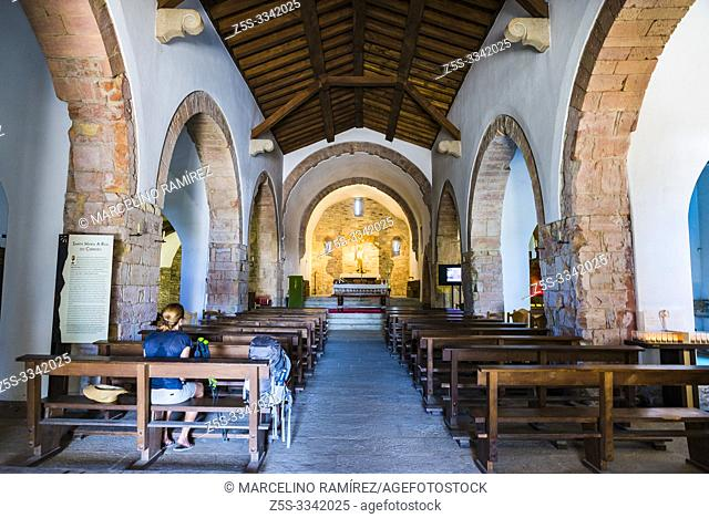 A pilgrim rests on a church bench. The Royal St. Mary's Church, also known as the Church of St. Benedict, was built in O Cebreiro in 1965â
