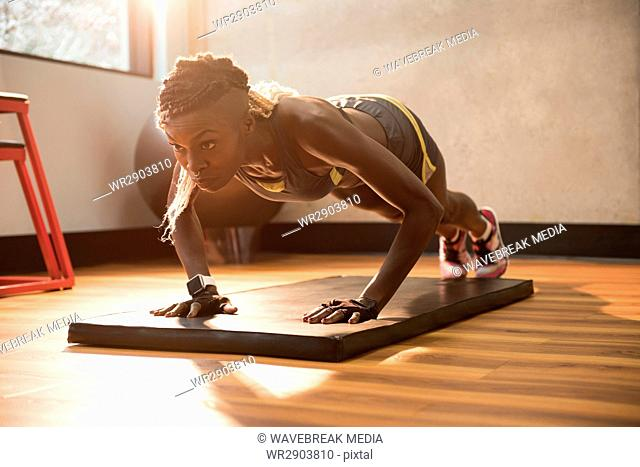 Fit woman performing push-up exercise on gymnastic mat