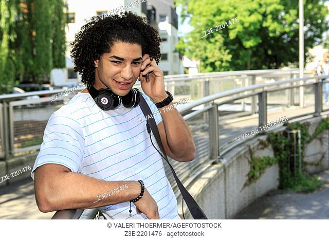 portrait of young male student with a phone in the town