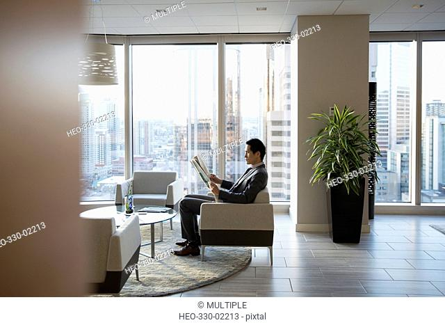 Businessman reading newspaper in highrise office lobby