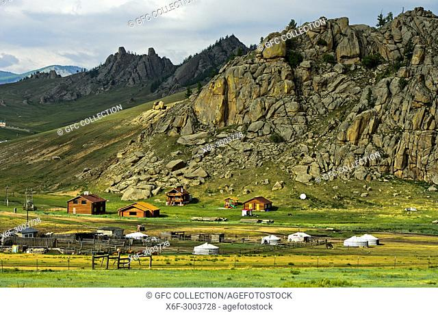 Hamlet with yurts and blockhouses in front of a rocky peak in the Mongolian steppe, Gorkhi-Terelj National Park, Mongolia