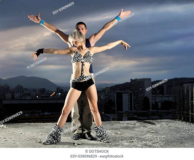 romantic urban couple dancing on top of the bulding at night scene