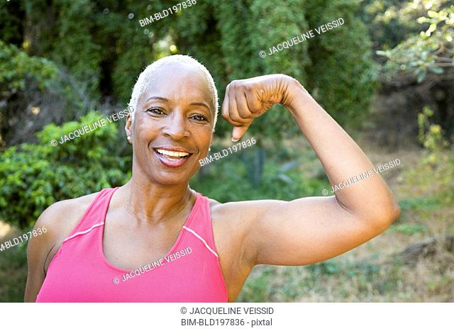 Mixed race woman flexing muscles outdoors