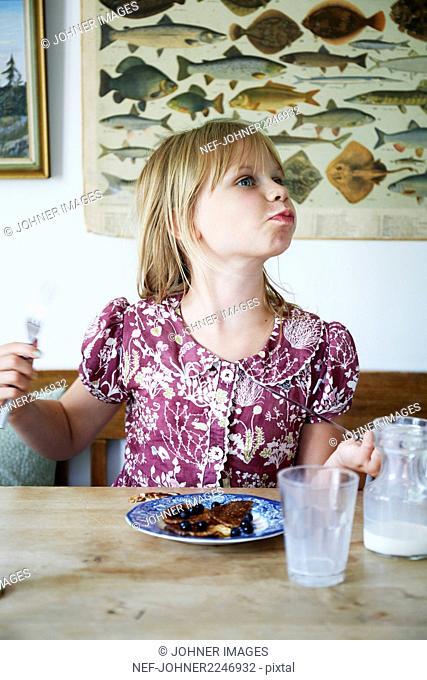Girl eating pancake with blueberries