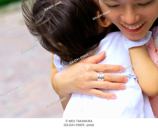 Close-up of a young woman embracing her daughter