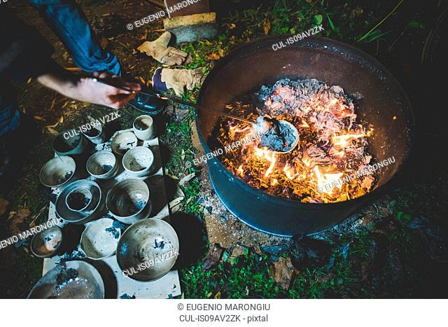 High angle view of young woman using tongs to remove clay pots from fire