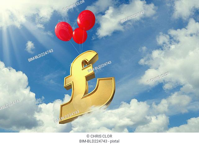 Red balloons lifting British pound symbol in cloudy sky