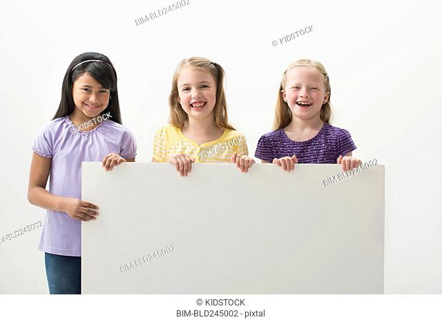 Portrait of smiling girls holding blank placard