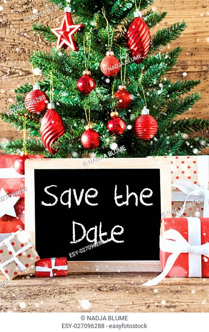 Chalkboard With English Text Save The Date. Colorful Christmas With Tree With Balls And Snowflakes. Gifts Or Presents In The Front Of Wooden Background