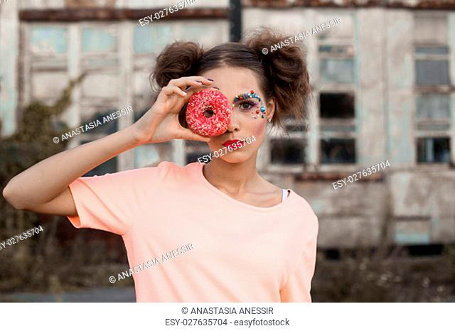 Fashion girl in pink t-shirt holding pink sweety donut