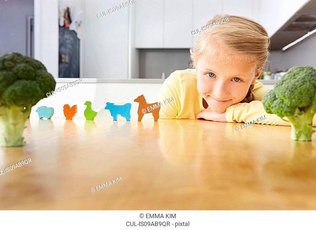 Girl playing with toy animals around broccoli