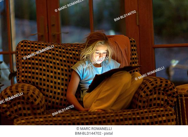 Caucasian girl using digital tablet in armchair at night