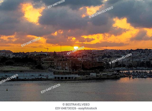 Golden hour on cloudy sky over buildings at Gzira area