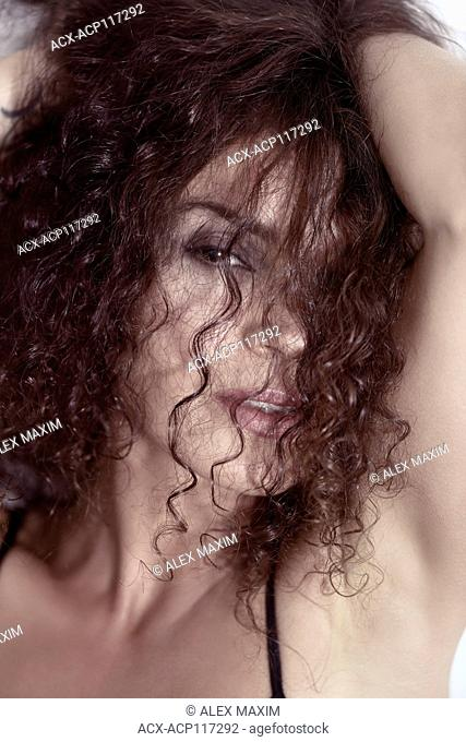 Closeup beauty face portrait of a young woman looking through her long curly brown hair with a sultry sensual look on her beautiful face