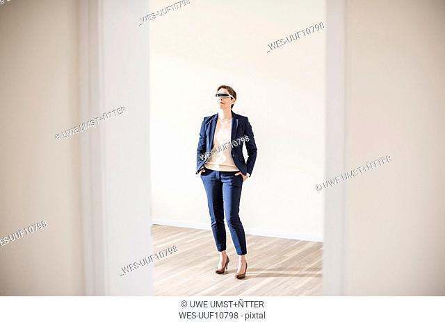 Woman in empty apartment wearing smartglasses