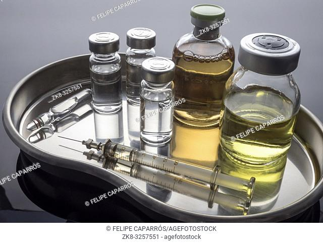 Vintage syringe next to vials with medication, conceptual image, horizontal composition