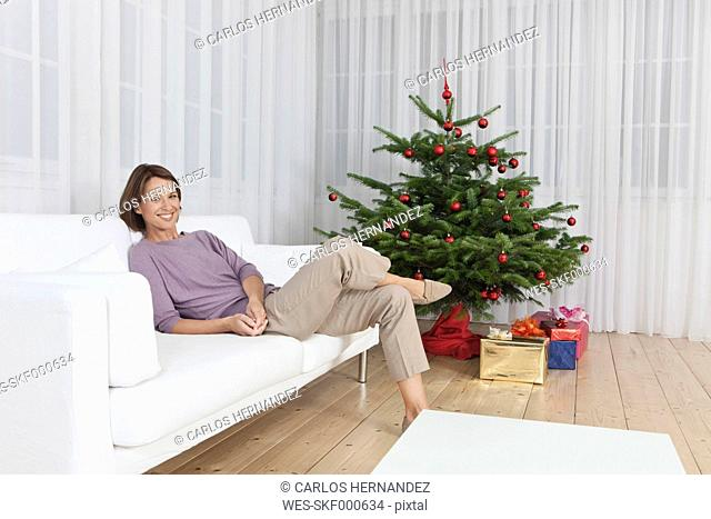 Germany, Munich, Woman sitting on couch near christmas tree, smiling, portrait