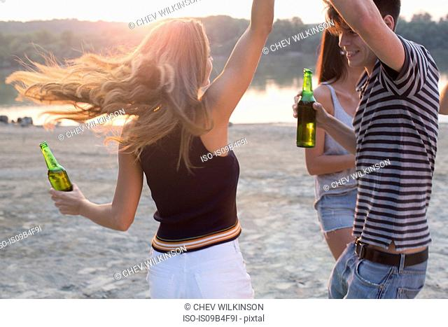 Group of friends drinking, enjoying beach party