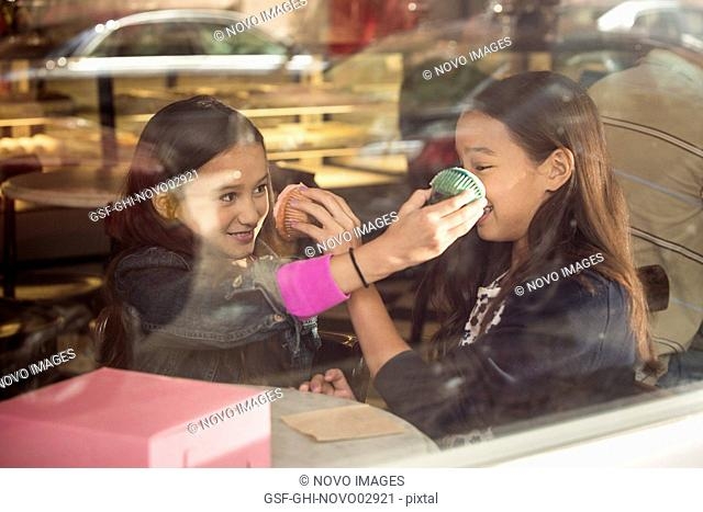 Two Young Girls Pushing Cupcakes into Each Other's Face