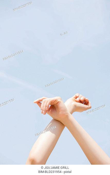 Hispanic woman crossing arms at wrist under blue sky
