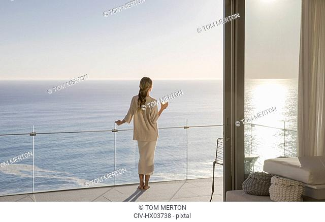 Woman standing on sunny luxury balcony with ocean view