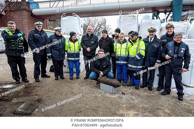 Security personnel and members of the bomb disposal team standing behind an aerial bomb from WWII for a souvenir photo in Frankfurt, Germany, 08 January 2017