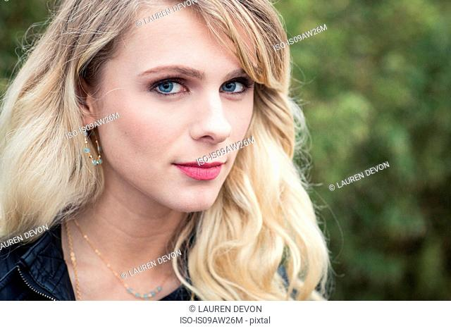Portrait of young blonde haired woman looking at camera