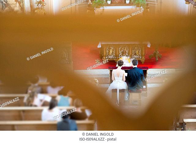 Bride and bridegrooms in front of altar in church