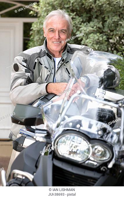 Portrait of confident senior man leaning on motorcycle