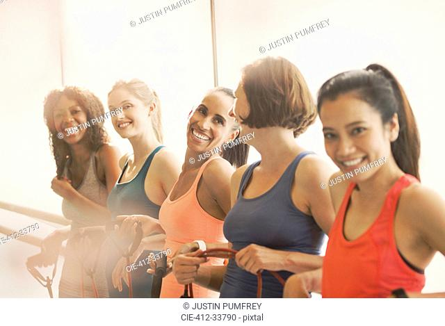 Smiling women holding resistance bands at barre in exercise class gym studio