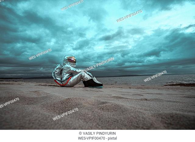Lonely spaceman looking at lake on nameless planet
