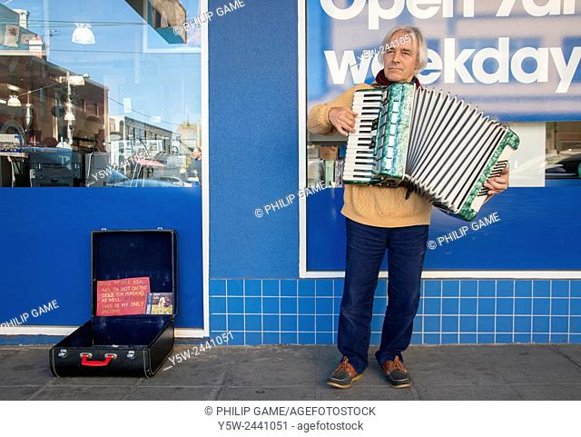 Middle-aged male musker playing an accordion in Glen Huntly Road, Elsternwick, Melbourne