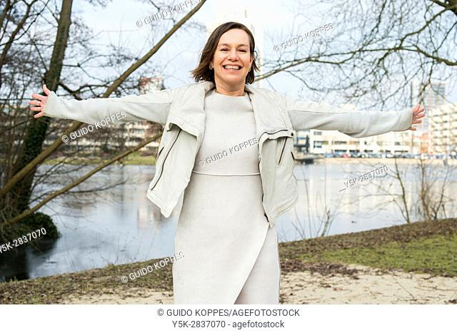 The Hague, Netherlands. Portrait of a happy and joyful caucasian woman in a park
