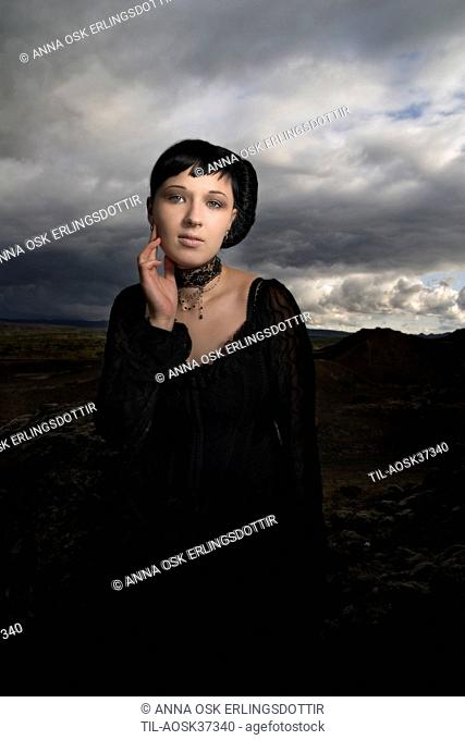 Lone female figure with black hair wearing black dress with rural countryside scene