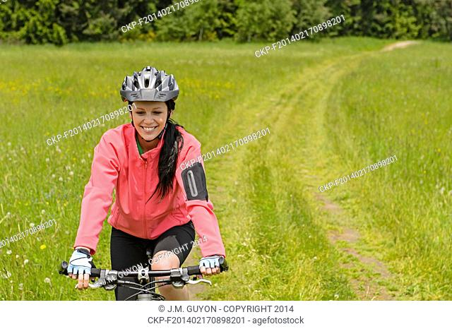 Woman riding bicycle on countryside path through meadow smiling