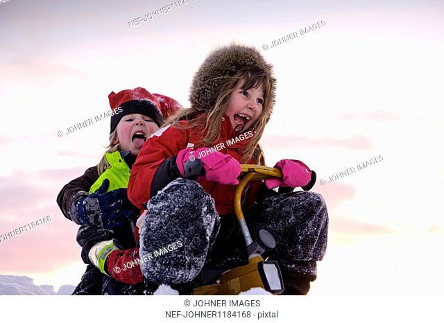 Children sledding in snow