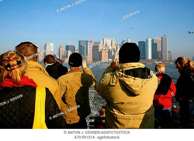 Tourists on boat, taking pictures of Manhattan's skyline. New York City. USA