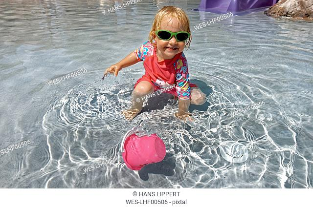 Clothed little girl with sunglasses playing in water