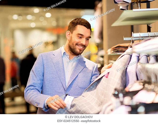 sale, shopping, fashion, style and people concept - happy young man in shirt choosing clothes in mall or clothing store