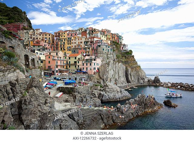 A view of Manarola with clear blue ocean and colourful buildings; Manarola, Liguria, Italy