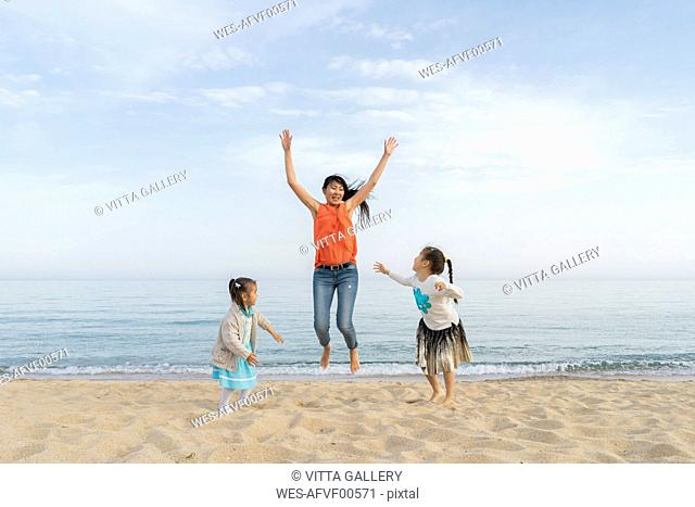 Happy mother with two daughters playing on the beach